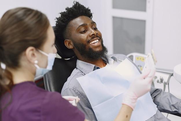 Jonge afro-amerikaanse man. man bezoekt het kantoor van de tandarts voor preventie van de mondholte. man en famale arts tijdens controle tanden. Gratis Foto