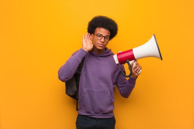 Jonge afro-amerikaanse man met een megafoon probeert een roddel te luisteren Premium Foto