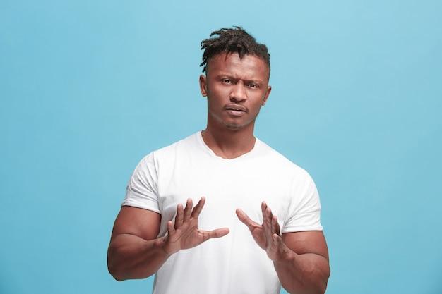 Jonge afro-amerikaanse man met weerzinwekkende uitdrukking iets afstoten, geïsoleerd op het blauw Gratis Foto