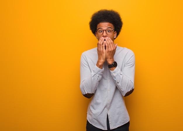 Jonge afro-amerikaanse man over een oranje muur erg bang en bang verborgen Premium Foto