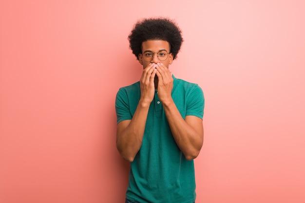 Jonge afro-amerikaanse man over een roze muur erg bang en bang verborgen Premium Foto