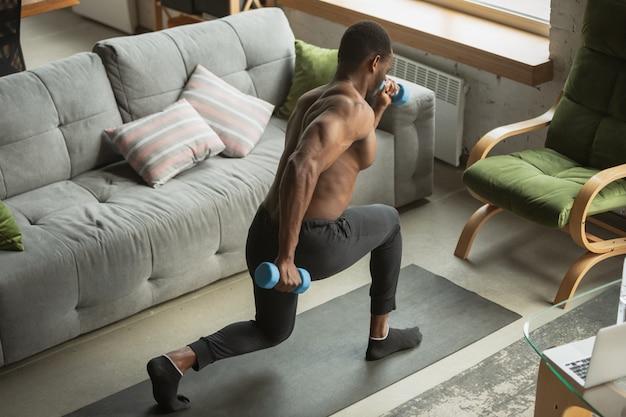 Jonge afro-amerikaanse man training thuis, het doen van fitness oefeningen, aërobe. Gratis Foto