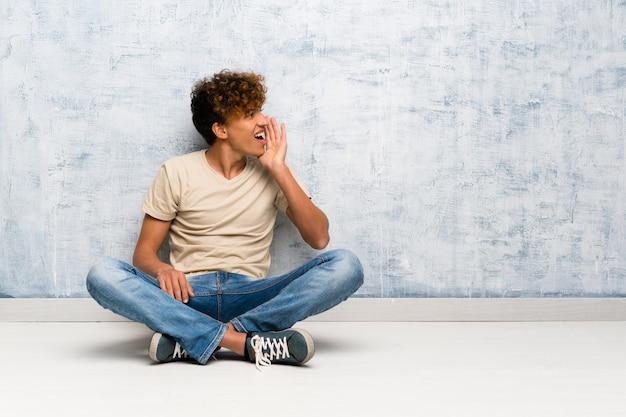 Jonge afro-amerikaanse man zittend op de vloer schreeuwen met mond wijd open voor de zijtak Premium Foto