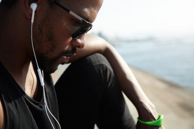 Jonge afro-amerikaanse rapper in zwarte top luisteren naar nieuwe nummers buiten onder de blauwe hemel. knappe en serieuze man zit alleen op de weg en chatten met zijn vrienden op zijn digitale apparaat. Gratis Foto