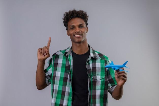 Jonge afro-amerikaanse reiziger man met speelgoed vliegtuig wijzende vinger omhoog lachend met zelfverzekerde uitdrukking op gezicht staande op witte achtergrond Gratis Foto