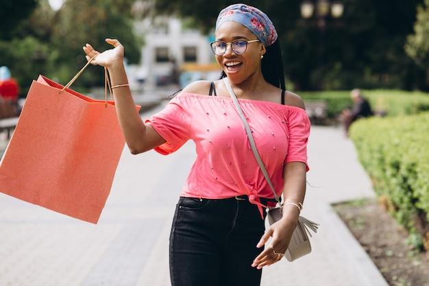Jonge afro-amerikaanse vrouw op straat met boodschappentassen Premium Foto