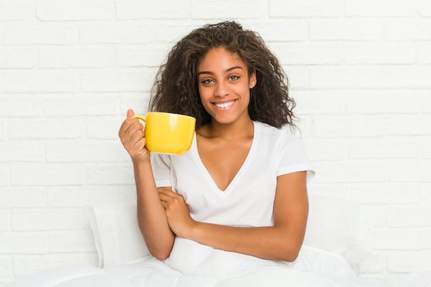 Jonge afro-amerikaanse vrouw zittend op het bed met een koffiemok glimlachend zelfverzekerd met gekruiste armen. Premium Foto