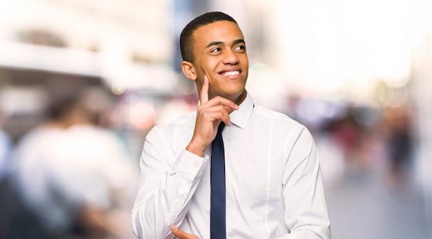Jonge afro amerikaanse zakenman die een idee denkt terwijl omhoog het kijken in de stad Premium Foto