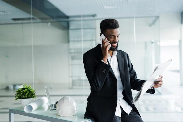 Jonge afro-amerikaanse zakenman krant lezen en praten over de telefoon in zijn kantoor Gratis Foto