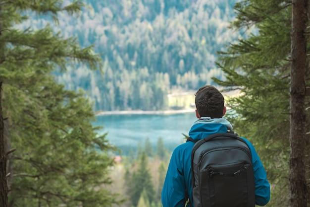 Jonge anonieme wandelaar met rugzak kijkt naar een bergmeer in de alpen Gratis Foto