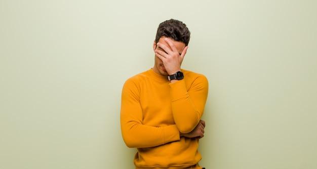 Jonge arabische mens die beklemtoond, beschaamd of verstoord, met hoofdpijn kijkt, die gezicht behandelt met hand tegen vlakke muur Premium Foto