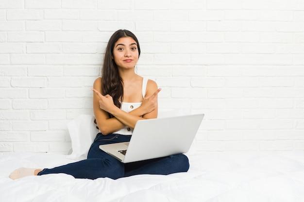 Jonge arabische vrouw die met haar laptop aan het bed werkt zijdelings Premium Foto