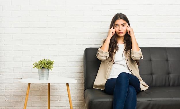 Jonge arabische vrouw zittend op de bank gericht op een taak, wijsvingers hoofd houden. Premium Foto