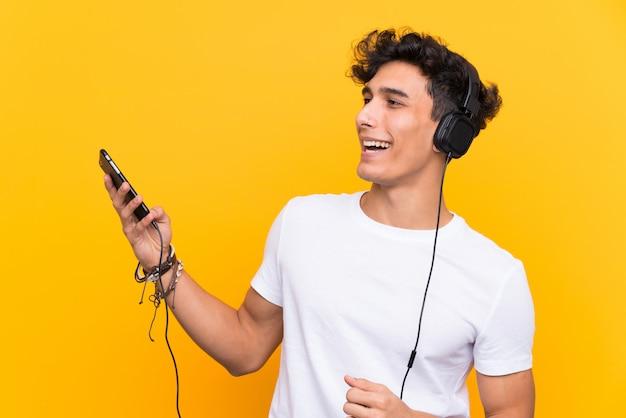 Jonge argentijnse man luisteren muziek met een mobiel over geïsoleerde gele muur Premium Foto