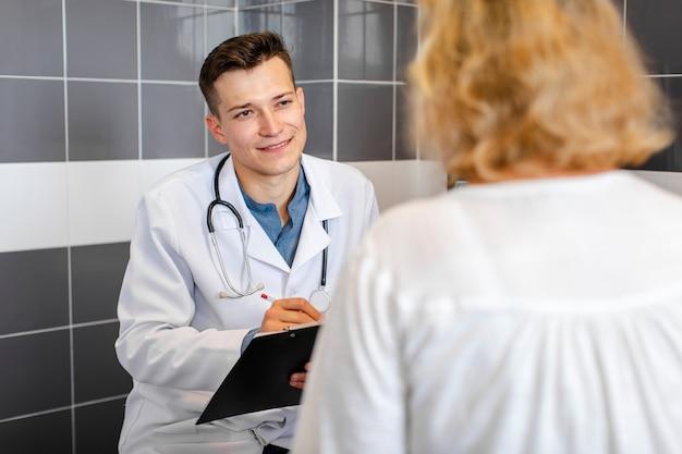 Jonge arts die met een patiënt in kabinet spreekt Gratis Foto