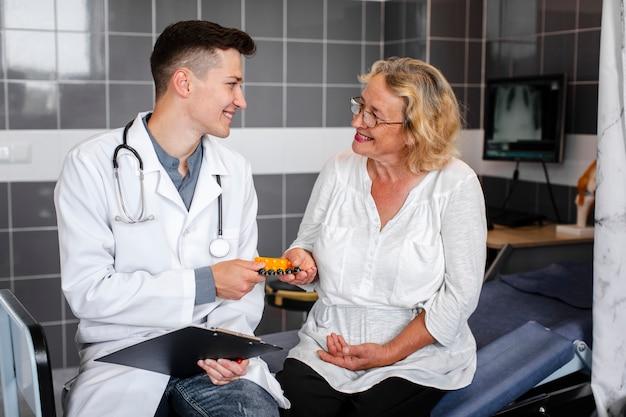 Jonge arts die pillen geeft aan vrouwelijke patiënt Gratis Foto