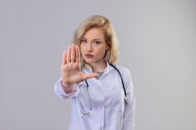 Jonge arts die stethoscoop in medische toga draagt die eindegebaar op witte muur toont Gratis Foto