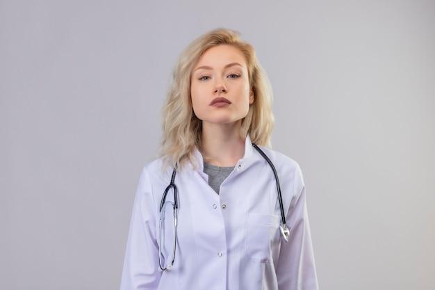 Jonge arts die stethoscoop in medische toga draagt op witte muur Gratis Foto