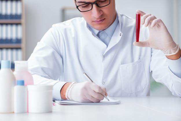 Jonge arts in het laboratorium met rode buis Premium Foto