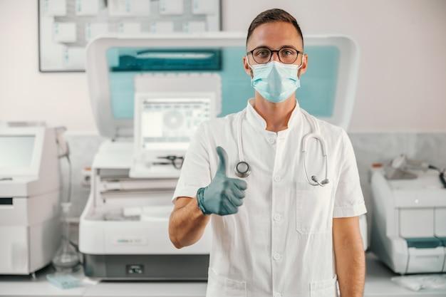 Jonge arts met rubberen handschoenen en gezichtsmasker staan in het ziekenhuis en duimen opdagen. Premium Foto