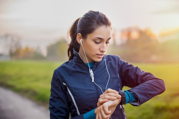 Jonge atleet luisteren naar muziek tijdens training in het park en slimme horloge aanpassen Premium Foto
