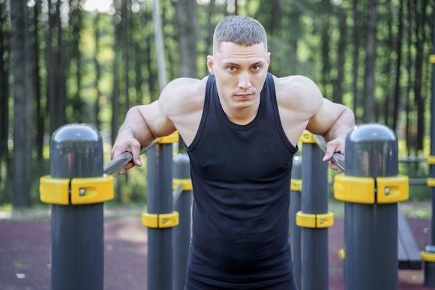 Jonge atletische man doet push-ups op bars buitenshuis. Premium Foto