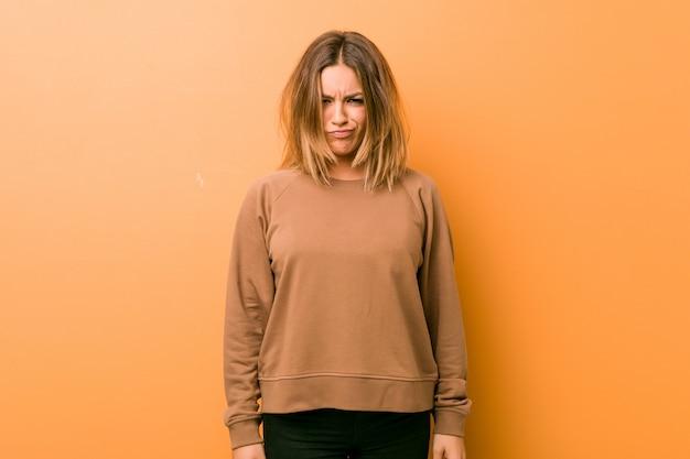 Jonge authentieke charismatische echte mensenvrouw tegen een muur blaast wangen, heeft vermoeide uitdrukking. gezichtsuitdrukking . Premium Foto
