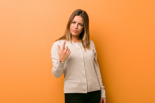 Jonge authentieke charismatische echte mensenvrouw tegen een muur die met vinger naar je wijst alsof je uitnodigt dichterbij te komen. Premium Foto