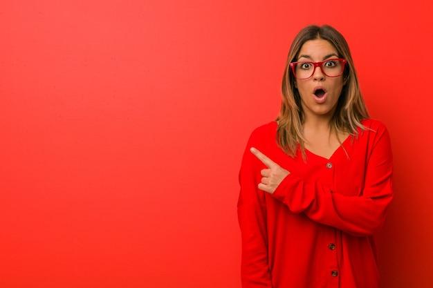 Jonge authentieke charismatische echte mensenvrouw tegen een muur die naar de zijkant wijst Premium Foto
