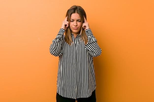 Jonge authentieke charismatische echte mensenvrouw tegen een muur gericht op een taak, waarbij wijsvingers het hoofd houden. Premium Foto