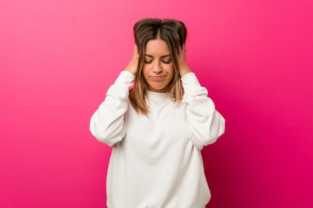 Jonge authentieke charismatische echte mensenvrouw tegen een muur wat betreft tempels en het hebben van hoofdpijn. Premium Foto