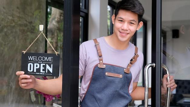 Jonge aziatische barista opent een glazen deur om klanten te verwelkomen. Premium Foto