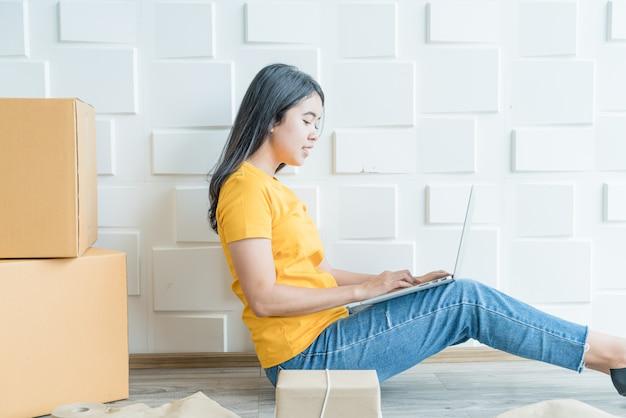 Jonge aziatische bedrijf start online verkoper-eigenaar met behulp van computer voor het controleren van de klantorders van e-mail of website en het voorbereiden van pakketten Premium Foto