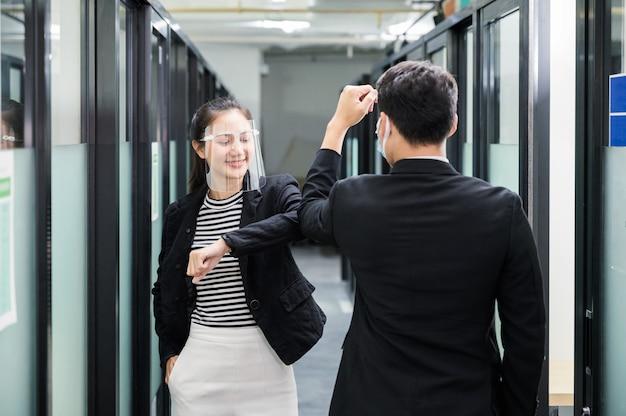 Jonge aziatische bedrijfscollega die gezichtsschild, gezichtsmasker en elleboogbuilgroet op gang in het bureau draagt Premium Foto