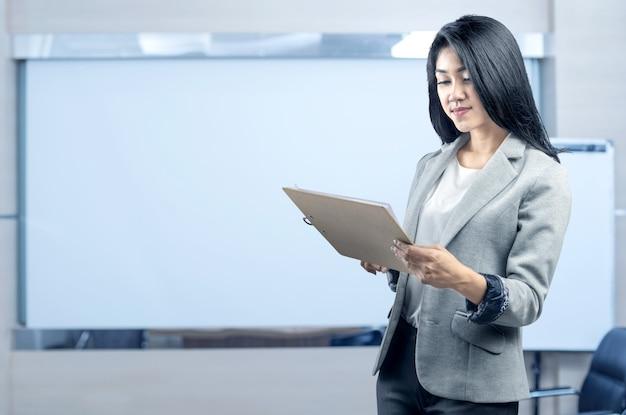 Jonge aziatische bedrijfsvrouw die en klembord bevindt zich houdt Premium Foto