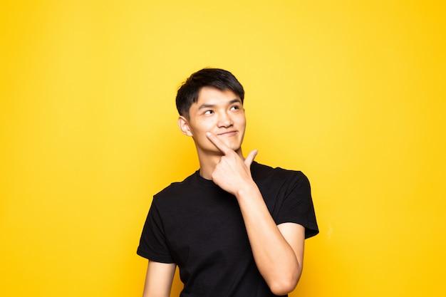 Jonge aziatische chinese mens die met hand op kin over vraag denkt, peinzende uitdrukking die zich over geïsoleerde gele muur bevindt. glimlachend met een bedachtzaam gezicht. twijfel concept. Gratis Foto