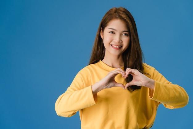 Jonge aziatische dame met positieve uitdrukking, toont handengebaar in hartvorm, gekleed in vrijetijdskleding en kijkt naar camera geïsoleerd op blauwe achtergrond. gelukkige schattige blije vrouw verheugt zich over succes. Gratis Foto