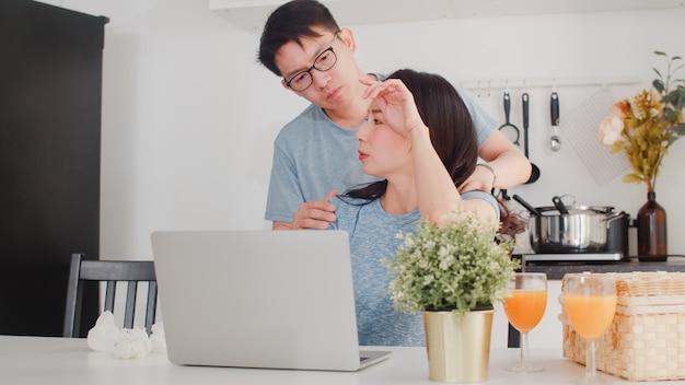 Jonge aziatische ernstige onderneemster, spanning, vermoeid en ziek terwijl thuis het werken aan laptop. man geeft haar glas water terwijl hij 's ochtends thuis hard aan het werk is in de moderne keuken. Gratis Foto