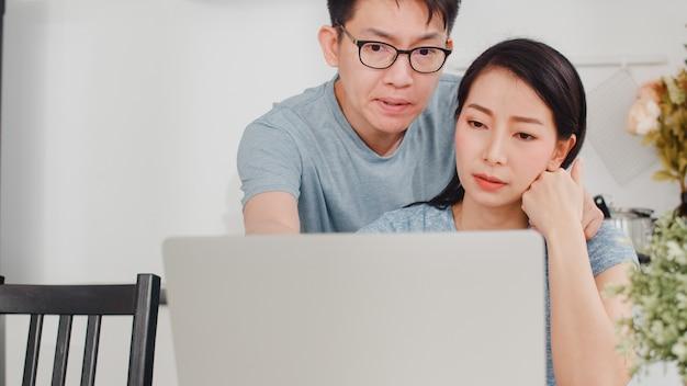 Jonge aziatische ernstige onderneemster, spanning, vermoeid en ziek terwijl thuis het werken aan laptop. man troost haar terwijl hij 's ochtends hard aan het werk is in de moderne keuken. Gratis Foto