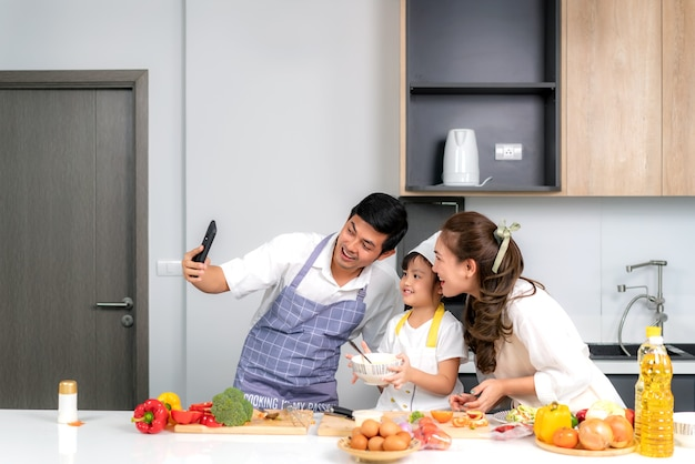Jonge aziatische familie bereiden salade in de keuken en vader neemt telefonisch een foto selfie Premium Foto