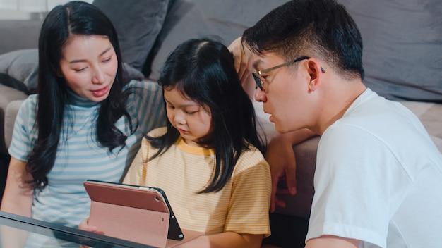 Jonge aziatische familie en dochter gelukkige thuis gebruikende tablet. de japanse moeder, vader ontspant met meisje het letten op film liggend op bank in woonkamer. de grappige ouder en het mooie kind hebben plezier. Gratis Foto