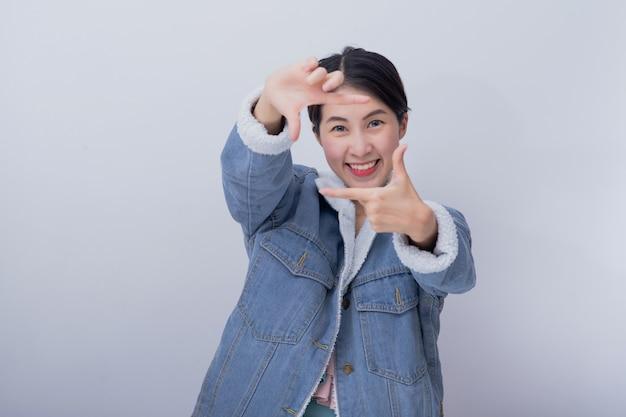 Jonge aziatische glimlachende opgewekte vrouw die haar hand met uitdrukking tonen die verrast en verbaasd voelen, positief kaukasisch meisje die blauwe vrijetijdskleding dragen Premium Foto