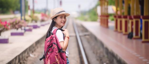 Jonge aziatische gril die bij station vóór reis loopt. Premium Foto