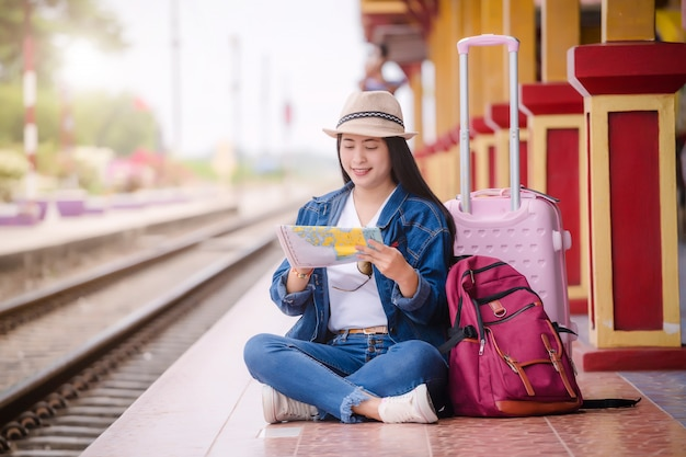 Jonge aziatische gril die bij station vóór reis lopen Premium Foto