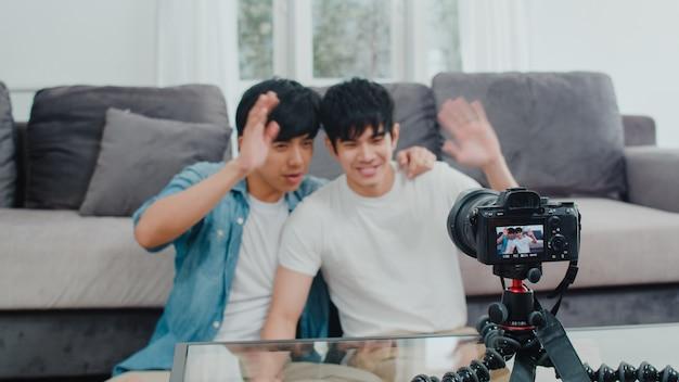 Jonge aziatische homo paar influencer paar vlog thuis. tiener koreaanse lgbtq mannen gelukkig ontspannen plezier met behulp van camera record vlog video-upload in sociale media terwijl liggend bank in woonkamer thuis. Gratis Foto