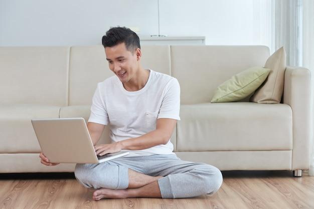Jonge aziatische kerel die zijn laptop op de vloer van de woonkamer naast de beige bank met behulp van Gratis Foto