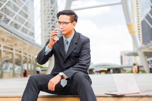 Jonge aziatische knappe zakenman die hete koffie in de moderne stad drinken. Premium Foto
