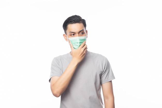 Jonge aziatische man met hygiënisch masker en denken om infectie, 2019-ncov of coronavirus te voorkomen. luchtwegaandoeningen zoals pm 2,5 vechten en griep geïsoleerd Premium Foto