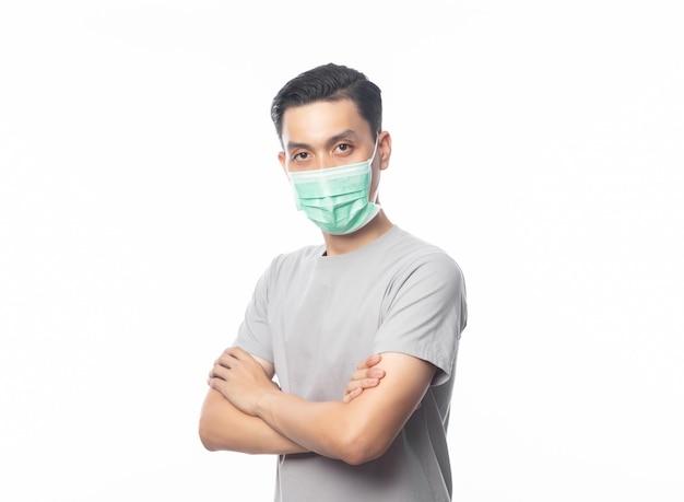 Jonge aziatische man met hygiënisch masker en gekruiste armen om infectie, 2019-ncov of coronavirus te voorkomen. luchtwegaandoeningen zoals pm 2,5 vechten en griep op wit wordt geïsoleerd Premium Foto