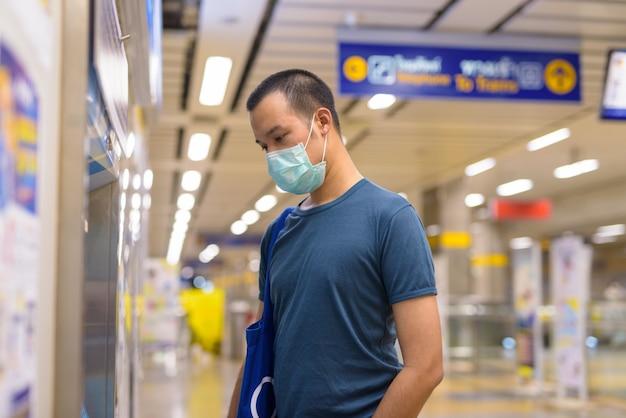 Jonge aziatische man met masker kaartje kopen bij het metrostation Premium Foto